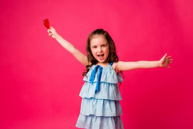 ピンクの背景笑顔に小さなブルネットの少女 Premium写真