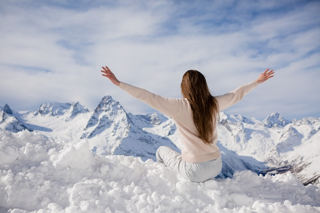 Молодая девушка в зимнем костюме смотрит на горы Premium Фотографии
