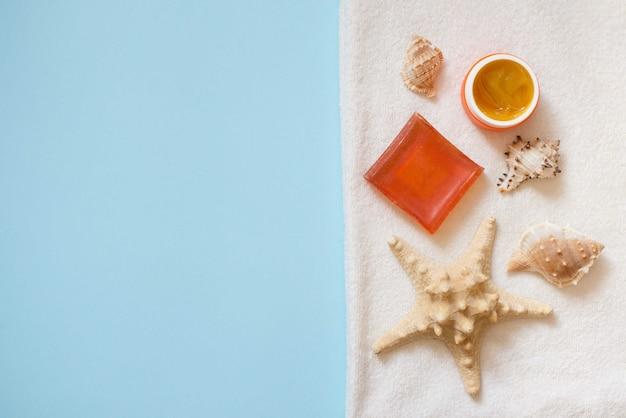 Косметические средства крем-апельсиновое мыло с ракушками и морская звезда на белом полотенце Premium Фотографии