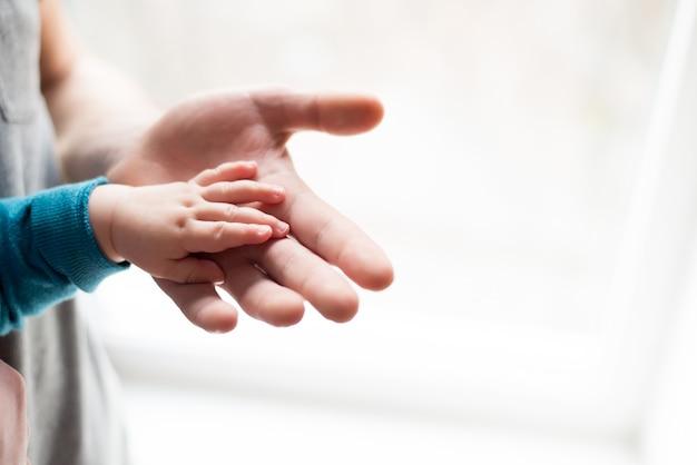 手をつないで。父のクローズアップの手で眠っている赤ちゃんを手します。 Premium写真