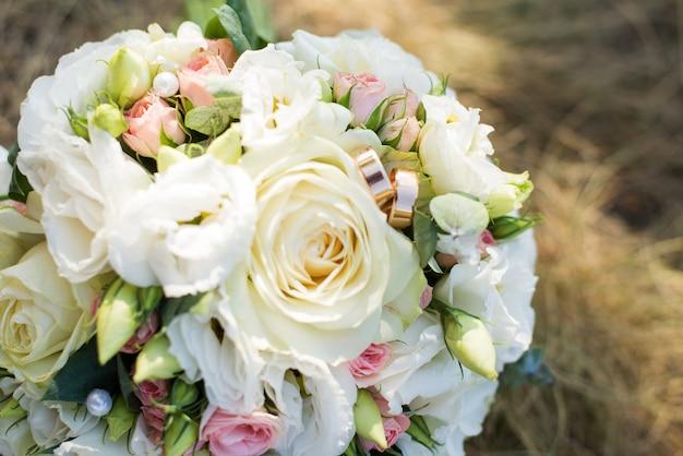 白い花と草の上のリングを持つ花嫁のブーケ Premium写真