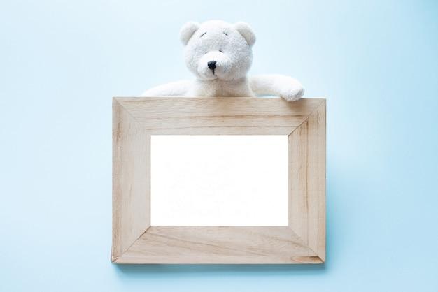 青の上に座って単一の白いテディベアと写真古い木枠。 Premium写真