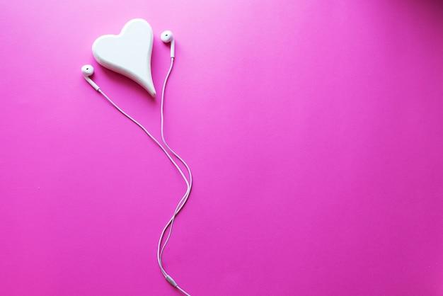 ピンクパステル調のプラスチックテクスチャ背景に白いイヤホンの平面図素敵なクローズアップ。 Premium写真