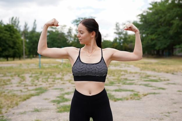強くてエネルギー。彼女の腕に力こぶを示すかなり若いブルネットの女性 Premium写真