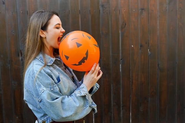 オレンジ色の空気風船を保持している女の子とハロウィーン秋の背景 Premium写真
