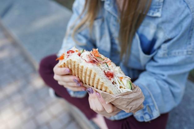 女の子は路上でシャワルマを食べる Premium写真