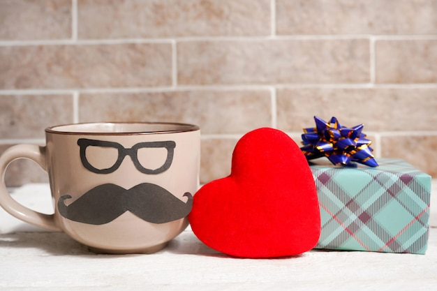 Кофейная чашка, сердце и подарочная коробка на деревянном столе. концепция праздника дня отца Premium Фотографии