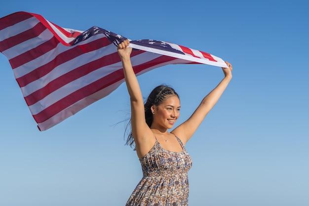 きれいで幸せな女の子は、空に対して米国の旗を保持しています。 Premium写真