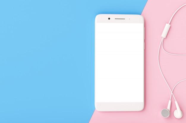 パステルカラーの背景にイヤホンを持つスマートフォン。 Premium写真