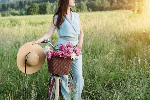自転車を保持している美しい女性の屋外のポートレート Premium写真