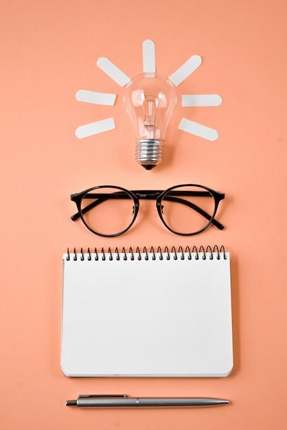 財務計画テーブルトップ、ペン、メモ帳、眼鏡、オレンジ色の背景上の電球。 Premium写真