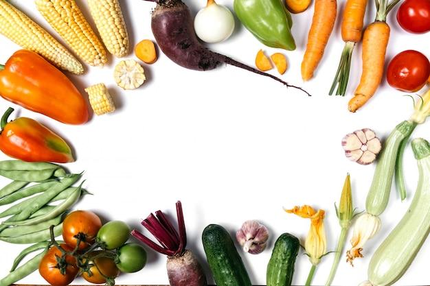 Помидоры, лук, огурец, морковь, чеснок, красная свекла, перец, цуккини, кукуруза и зеленая фасоль на белом фоне. Premium Фотографии