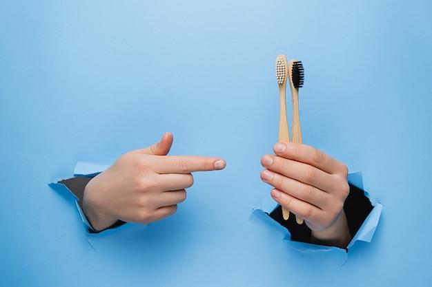 引き裂かれた青い紙の壁を通して竹エコ歯ブラシで指している認識できない女性。 Premium写真