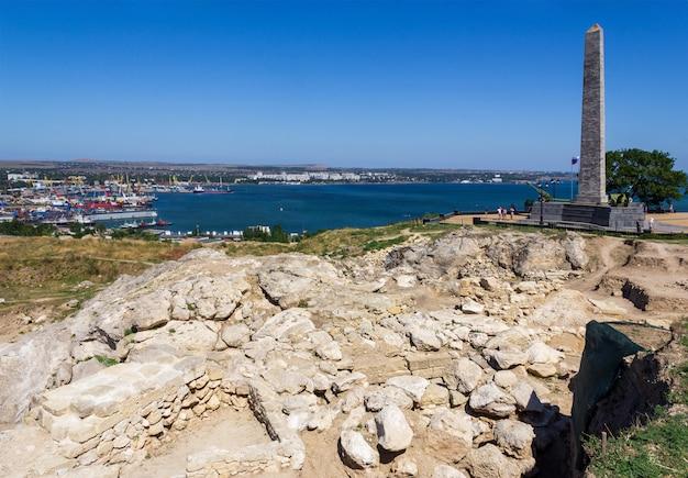 Археологические раскопки на руинах древнегреческого города пантикапей с видом на обелиск славы бессмертным героям на горе митридат и на черном море. Premium Фотографии