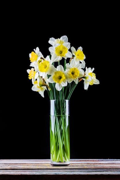 黒の背景にテーブルの上の花瓶に水仙の花の花束 Premium写真