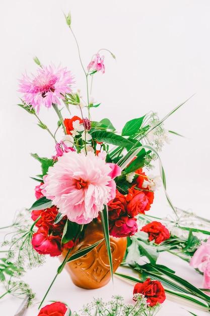 花柄のデザイン。ピンクの牡丹、ヤグルマギク、赤いバラの美しい花束 Premium写真
