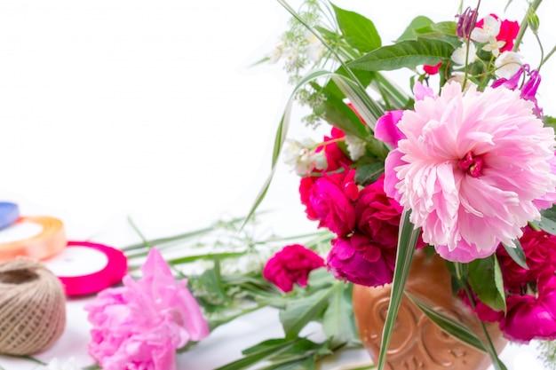 ピンクの牡丹の花、ヤグルマギクと赤いバラの美しい花束とフラワーアレンジメント Premium写真