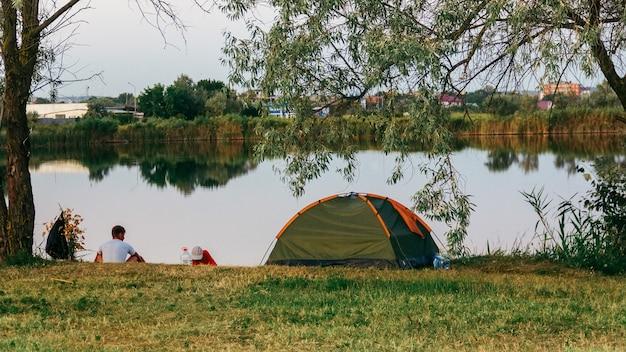 夏の夜に湖のほとりにテントがあり、二人の男が釣りに行く Premium写真