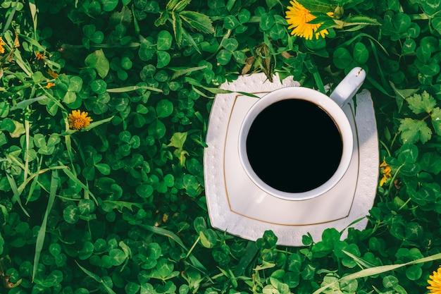 緑のクローバートップビューのクローズアップと草原のブラックコーヒーと白いカップ Premium写真