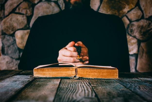 古い開かれた本の前で祈る祈りのビーズを手に黒い服を着た男。 Premium写真