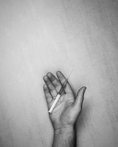 Медицинский шприц с иглой и наркотиками на открытой мужской ладони на сером фоне Premium Фотографии