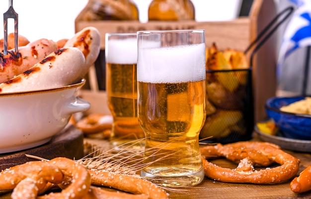 木製の泡と新鮮なビール。オクトーバーフェストドイツのプレッツェル。 Premium写真