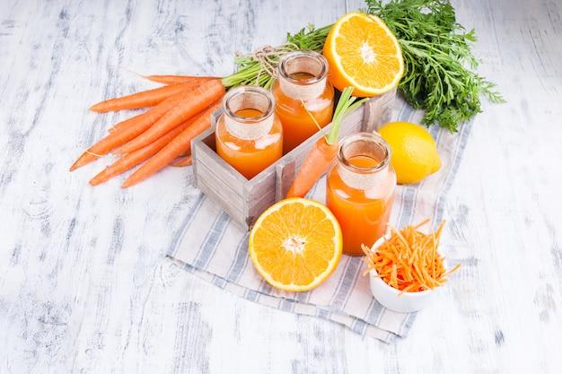 ニンジン、オレンジ、レモンのフレッシュジュース。葉と木の背景に他の新鮮な果物とニンジン。 Premium写真