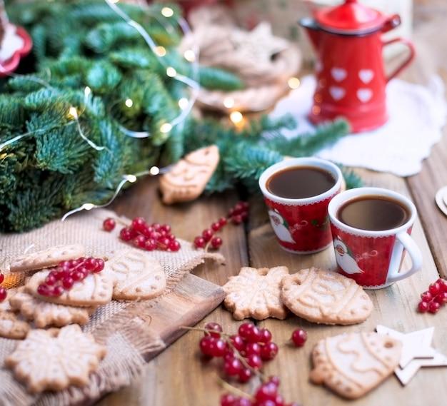 Две маленькие чашки кофе и кофейник, торт с ягодами и печеньем, подарки, возле елки на деревенском столе возле окна Premium Фотографии