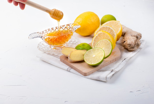 ハーブ、レモン、ジンジャーホワイトバックグラウンドと蜂蜜とお茶 Premium写真