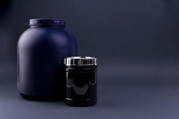 黒い背景に瓶にスポーツ栄養。カクテル用のプロテインパウダー。テキスト用の空きスペース。コピースペース、 Premium写真