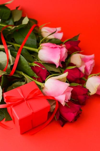 女性の日の概念とバレンタインのグリーティングカード。ギフト、バラ、封筒のコンポジション。テキスト用のスペース。 Premium写真