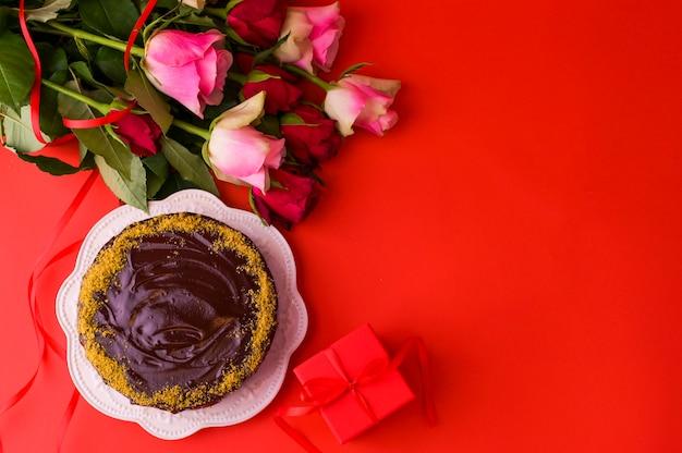 コンセプト女性の日または聖バレンタインの日。新鮮なバラと赤い背景のギフトボックスとチョコレートケーキ。上面図。コピースペース Premium写真