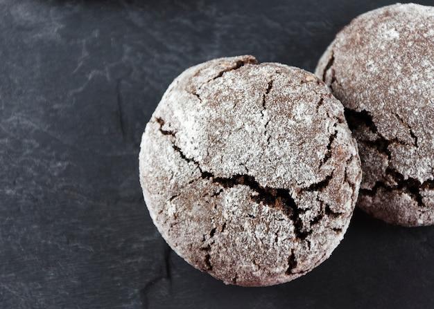 チョコレートしわ。粉砂糖入りチョコレートクッキー Premium写真