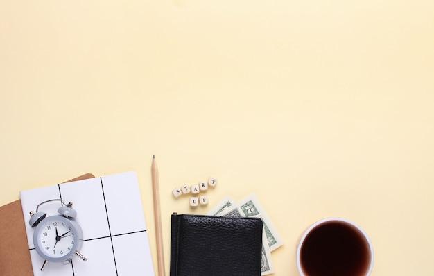 鉛筆、財布、目覚まし時計、木製の文字の単語起動でベージュ色の背景にコーヒーのカップを持つノートブック。 Premium写真