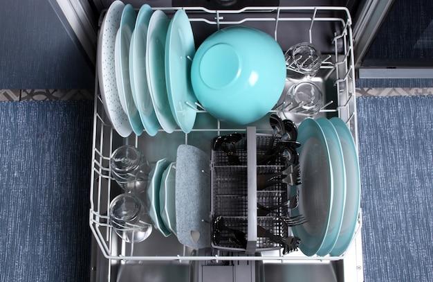 食器洗い機を開いてください。上面図。食器洗い機での洗浄後、皿、グラス、フォーク、スプーンをきれいにしてください。洗浄プロセス後の食器洗い機。 Premium写真