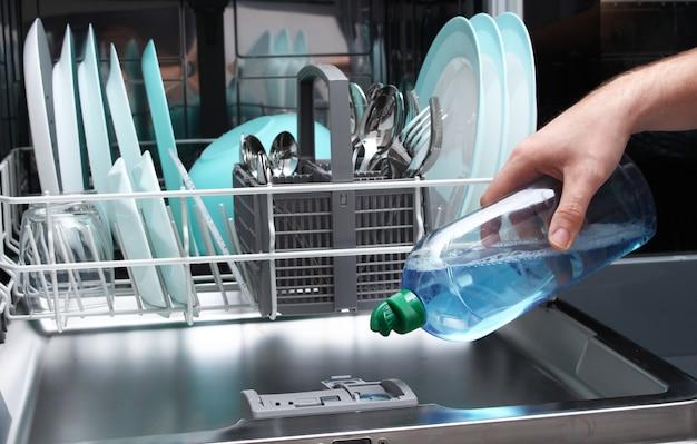光沢液を食器洗い機に入れます。光沢のある液体で男充填食器洗い機。 Premium写真