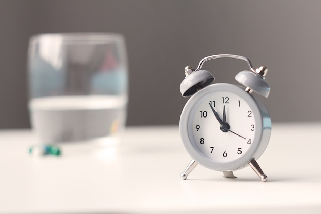 目覚まし時計とベッドサイドテーブルの上の医療薬。ヘルスケアと薬。 Premium写真