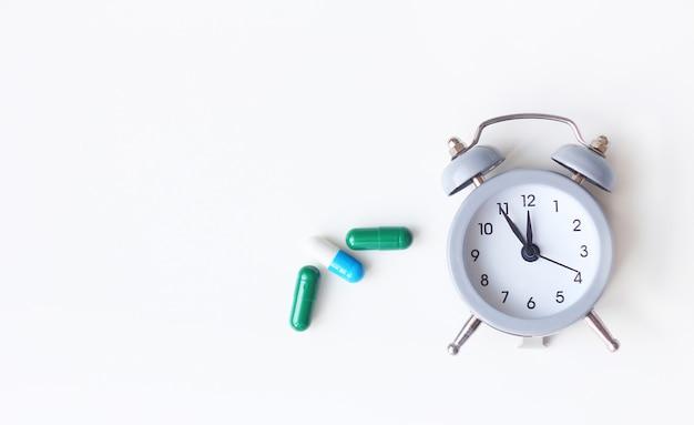 目覚まし時計と白い背景の上の医療薬 Premium写真