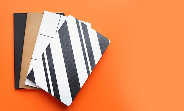 学校コンセプト、学用品、カラフルなノートブックの明るいオレンジ色の背景のトップビューに戻る Premium写真