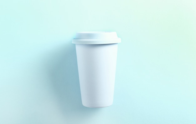 パステルブルーセラミックトラベルマグカップブルー。トップビュー、フラットレイアウト。青のタンブラーカップ。 Premium写真