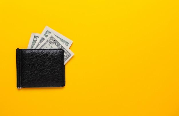 黄色の背景にドル紙幣と黒の財布。フラット横たわっていた、トップビュー、コピースペース。 Premium写真
