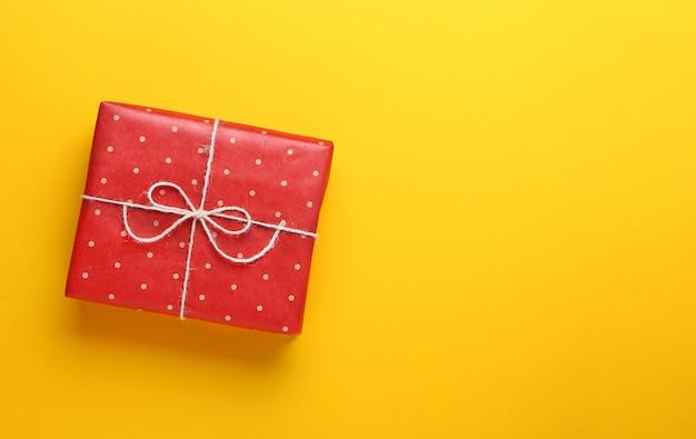 黄色の背景に赤いクラフト水玉紙に包まれた贈り物。 Premium写真