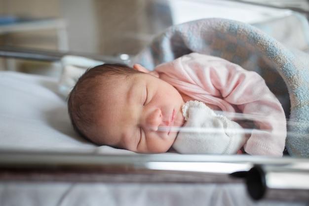 Новорожденный ребенок в больнице лежит в коробке. маленький ребенок спит сразу после рождения. Premium Фотографии