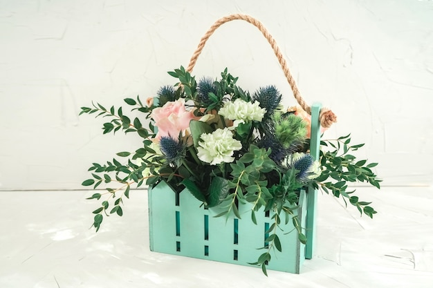 Симпатичная бирюзовая корзинка с букетом. свадебные цветы для оформления ресторана Premium Фотографии