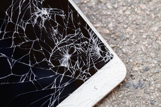 壊れた青い表示画面を持つスマートフォンはアスファルトの上に横たわっています。 Premium写真