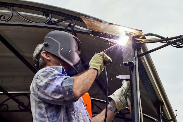 Сварщик с защитной маской для сварки металла выполняет сварочные работы Premium Фотографии