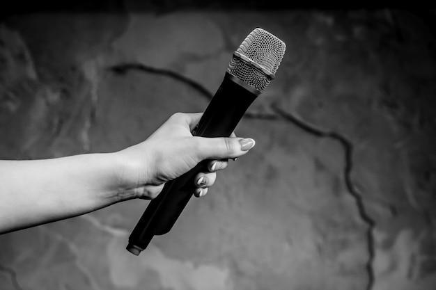 Женщина, держащая микрофон на сером фоне, крупным планом. белое и черное фото. Premium Фотографии