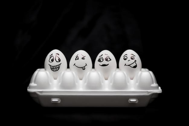 Настоящие яйца с ручной росписью. белые яйца с лица обращается в коробке. Premium Фотографии
