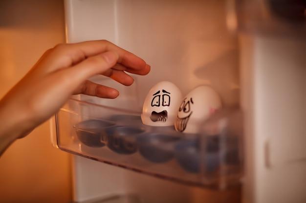 Эмоционально яйца. женская рука эмоционально берет яйцо с подноса холодильника. Premium Фотографии