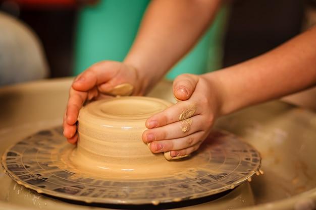 陶器のホイールにセラミックポットを作るための陶芸家の子供 Premium写真